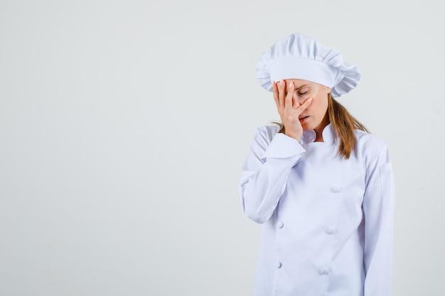 Kobieta kucharz w białym mundurze trzymając rękę na twarzy z zamkniętymi oczami i wyglądając na zmęczonego