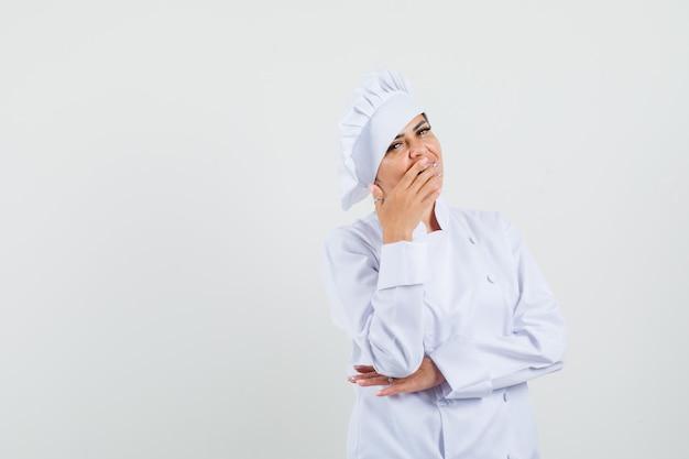 Kobieta kucharz w białym mundurze, trzymając rękę na ustach i patrząc zaskoczony
