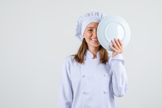 Kobieta kucharz w białym mundurze trzymając talerz w pobliżu twarzy i patrząc zadowolony