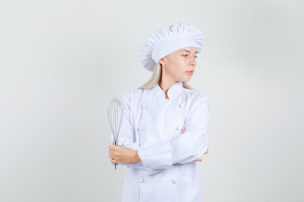 Kobieta kucharz w białym mundurze trzymając trzepaczkę i patrząc na bok