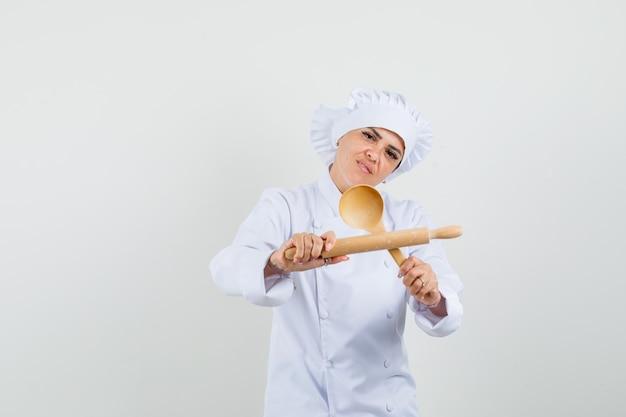 Kobieta kucharz w białym mundurze, trzymając wałek do ciasta i drewnianą łyżkę i wyglądający pewnie