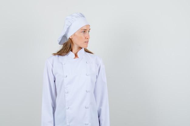 Kobieta kucharz w białym mundurze, wpatrując się w bok i patrząc poważnie