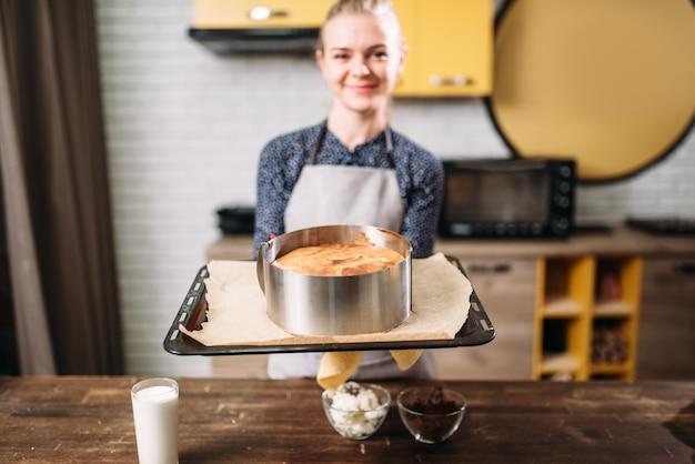Kobieta kucharz w fartuch trzyma patelnię z świeżym ciastem.