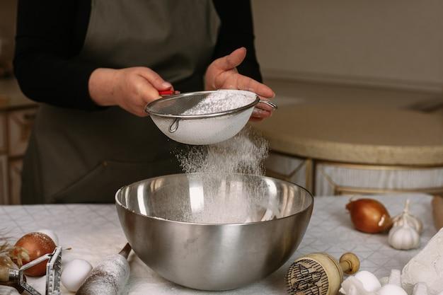 Kobieta kucharz w fartuchu przesiewa mąkę w metalowej misce. przygotowanie do przygotowania ciasta do pieczenia lub rzeźbienia dań gotowych.