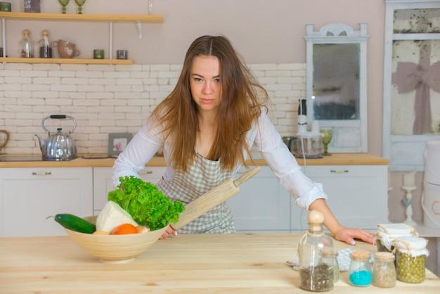 Kobieta kucharz w kuchni z wałkiem w dłoniach.