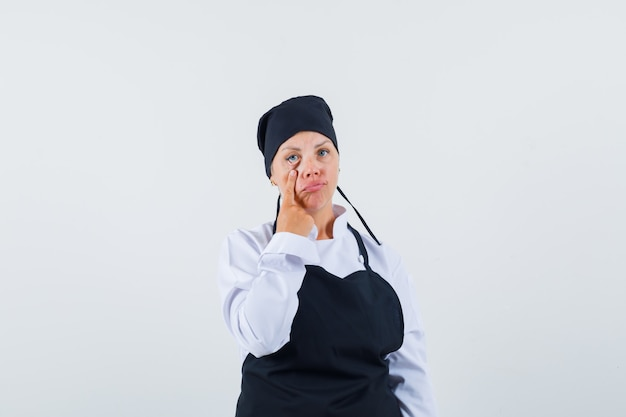 Kobieta kucharz w mundurze, fartuch odciągający powiekę i wyglądający na wyczerpanego, widok z przodu.