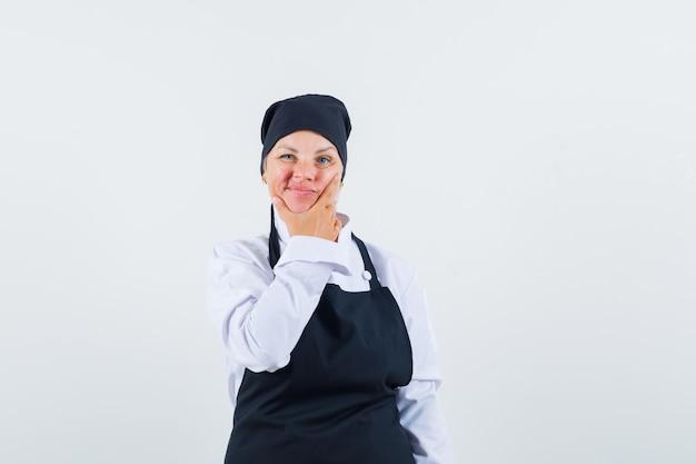 Kobieta kucharz w mundurze, fartuch, trzymając ją pod brodą i niepewny, patrząc z przodu.