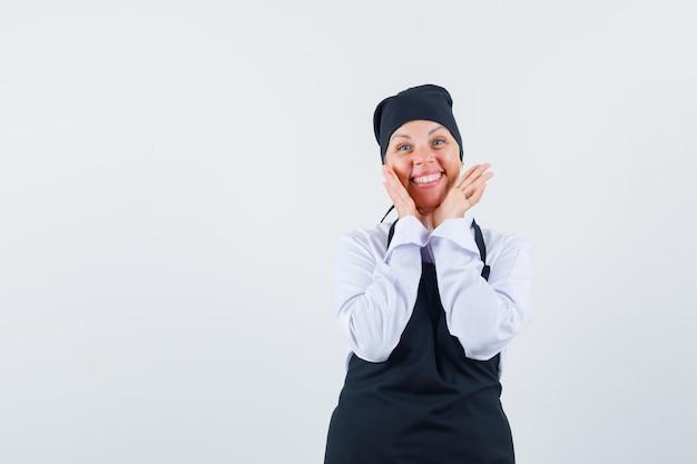 Kobieta kucharz w mundurze, fartuch trzymając się za ręce w pobliżu policzków i wyglądający uroczo, widok z przodu.