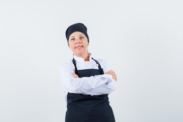Kobieta kucharz w mundurze, stojący fartuch ze skrzyżowanymi rękami i wyglądający pewnie, widok z przodu.