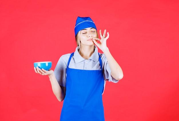 Kobieta kucharz w niebieskim fartuchu trzyma kubek z makaronem i pokazuje znak zadowolenia