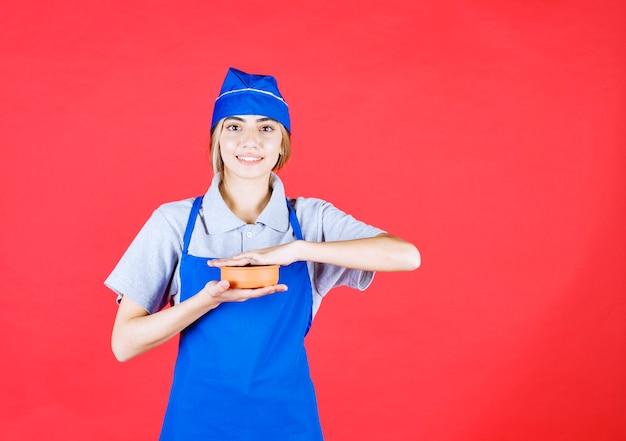 Kobieta kucharz w niebieskim fartuchu trzyma kubek z makaronem między rękami