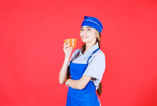 Kobieta kucharz w niebieskim fartuchu trzyma kubek z makaronem