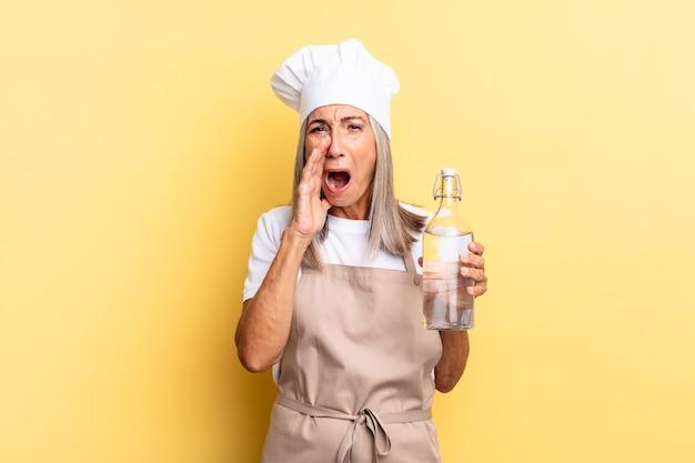 Kobieta kucharz w średnim wieku czuje się szczęśliwa, podekscytowana i pozytywna, wydając wielki okrzyk z rękami przy ustach, wołając butelkę wody