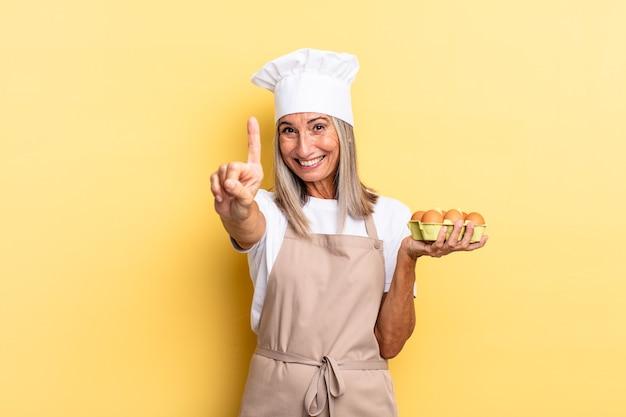 Kobieta kucharz w średnim wieku uśmiecha się dumnie i dumnie, triumfalnie wykonując pozę numer jeden, czując się jak lider trzymający pudełko z jajkami