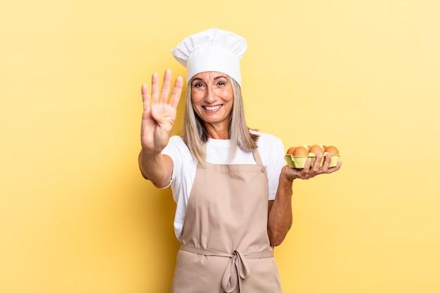 Kobieta kucharz w średnim wieku uśmiechnięta i wyglądająca przyjaźnie, pokazująca cyfrę cztery lub czwartą z ręką do przodu, odliczającą trzymającą pudełko z jajkami
