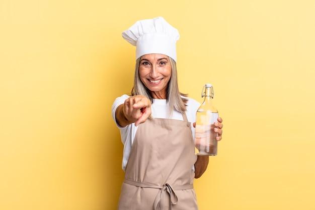 Kobieta Kucharz W średnim Wieku, Wskazująca Na Aparat Z Zadowolonym, Pewnym Siebie, Przyjaznym Uśmiechem, Wybierająca Cię Z Butelką Wody Premium Zdjęcia