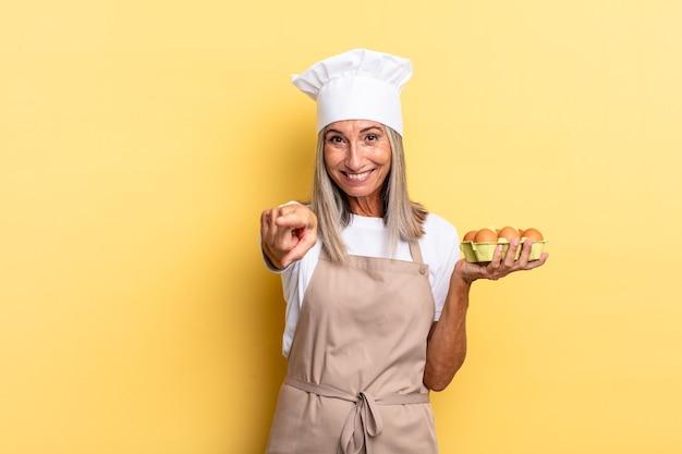 Kobieta kucharz w średnim wieku, wskazująca na aparat z zadowolonym, pewnym siebie, przyjaznym uśmiechem, wybierająca ciebie trzymającego pudełko z jajkami
