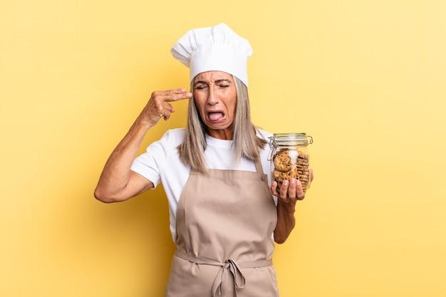 Kobieta kucharz w średnim wieku wyglądająca na nieszczęśliwą i zestresowaną, samobójczy gest wykonujący znak pistoletu ręką, wskazujący na głowę z ciasteczkami