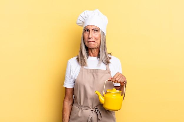 Kobieta kucharz w średnim wieku wyglądająca na zdziwioną i zdezorientowaną, gryzącą wargę nerwowym gestem, nie znającą odpowiedzi na problem i trzymającą czajnik