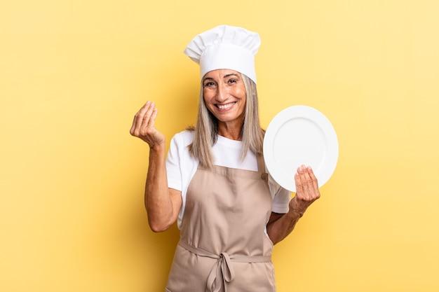 Kobieta kucharz w średnim wieku wykonująca gest kaprysu lub pieniędzy, mówiąca o spłacie długów! i trzyma naczynie