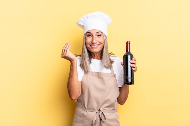 Kobieta kucharz w średnim wieku wykonująca gest kaprysu lub pieniędzy, mówiąca o spłacie długów! trzyma butelkę wina