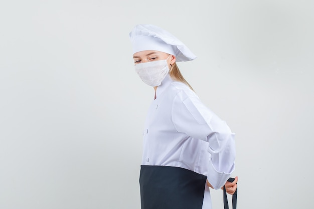 Kobieta kucharz wiązanie fartucha wokół talii w białym mundurze, maska medyczna.