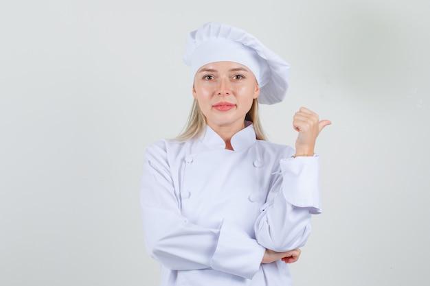Kobieta kucharz wskazując kciukiem w bok w białym mundurze i wyglądający wesoło