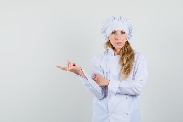 Kobieta kucharz, wskazując na bok w białym mundurze