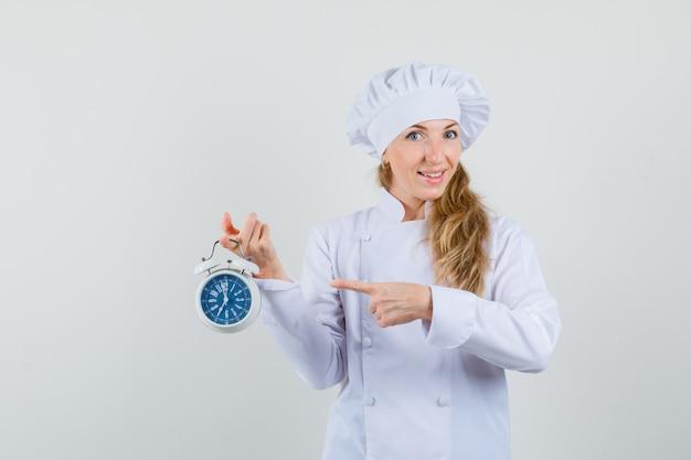 Kobieta kucharz, wskazując na budzik w białym mundurze i patrząc wesoło
