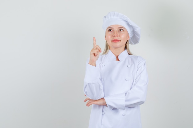 Kobieta kucharz wskazując palcem i uśmiechając się w białym mundurze