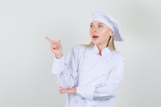 Kobieta kucharz wskazując palcem w białym mundurze i patrząc pozytywnie