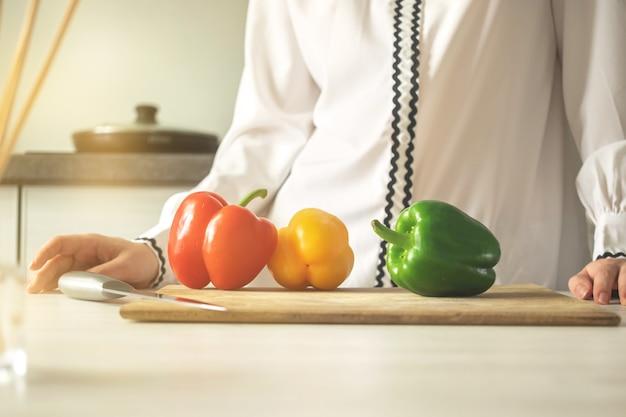 Kobieta kucharz z deską do krojenia i czerwona, żółta i zielona słodka papryka. składnik warzywny, gotowanie zdrowej żywności koncepcja zdjęcie