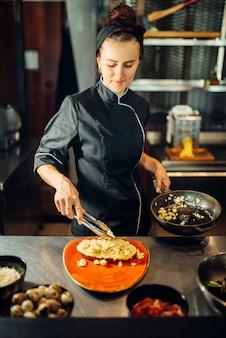 Kobieta kucharz z patelni, gotowanie mięsa z makaronem na drewnianym stole. dekorowanie na befsztyk, przygotowanie potraw w kuchni