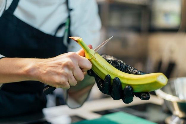 Kobieta kucharz z rękawiczki cięcia banana
