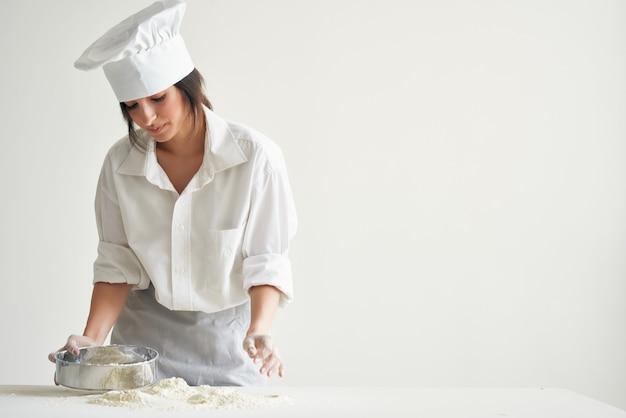 Kobieta kucharzy jednolita wyrabiająca ciasto pracująca z profesjonalną mąką