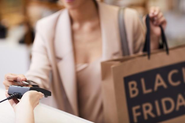 Kobieta kupno ubrań w butiku z bliska
