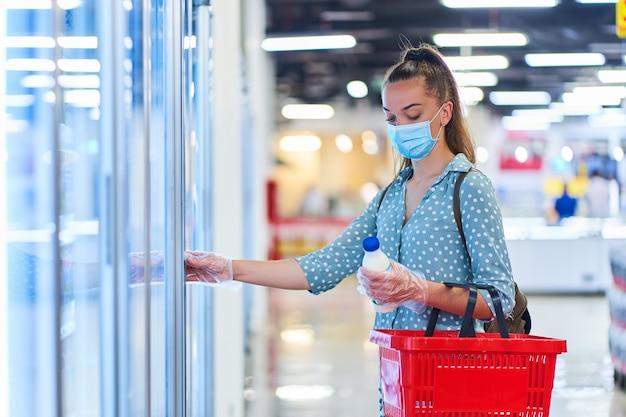 Kobieta kupująca w medycznej ochronnej masce z koszem na zakupy wybiera produkty mleczne z zamrażarki w sklepie spożywczym