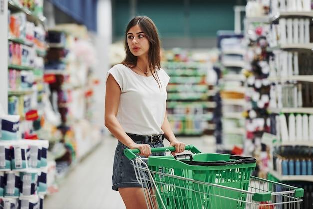 Kobieta kupująca w zwykłych ubraniach na rynku, szukająca produktów.