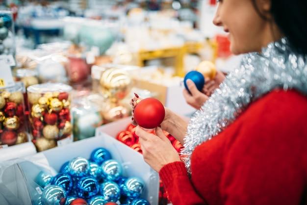 Kobieta kupuje bombki choinkowe w supermarkecie, rodzinna tradycja. grudniowe zakupy artykułów świątecznych