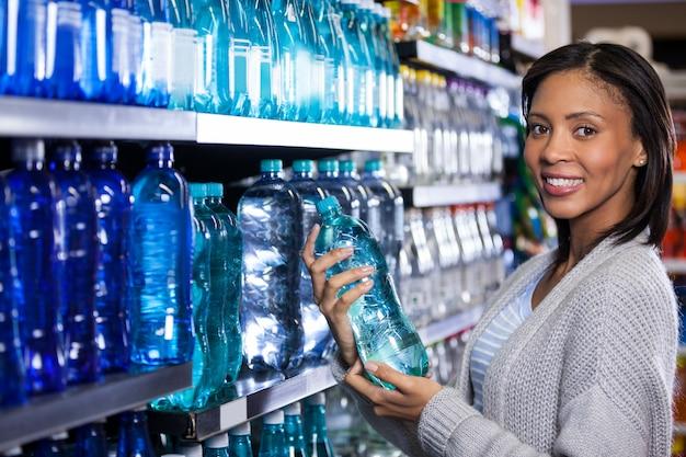 Kobieta kupuje butelkę wody