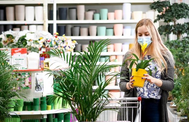 Kobieta kupuje kwiaty koszyk garden center