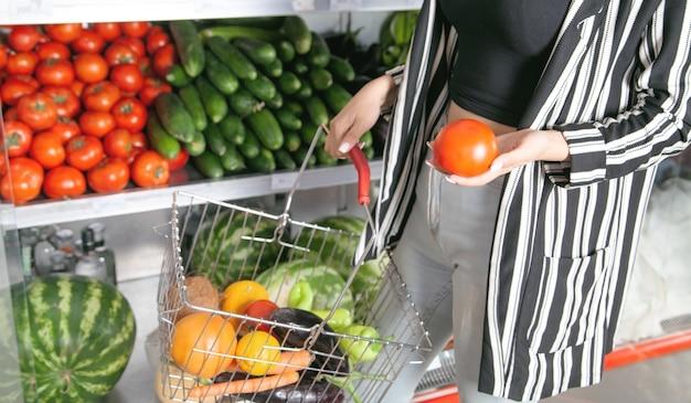 Kobieta kupuje pomidory w sklepie spożywczym.