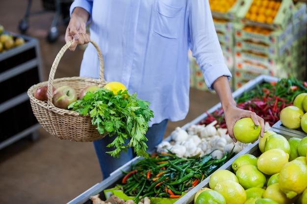 Kobieta kupuje słodkiego wapno w organicznie sekci