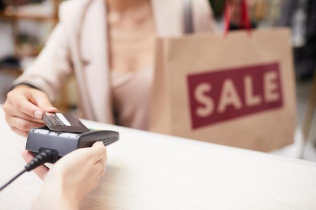 Kobieta kupuje ubrania na sprzedaż w butiku