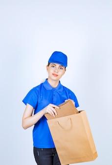 Kobieta kurier biorąc karton z torby papierowej.