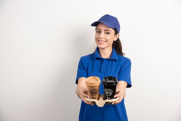 Kobieta kurier dając filiżanki kawy.