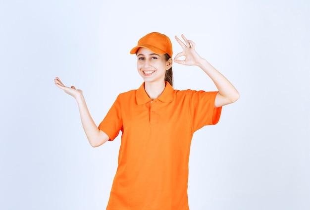 Kobieta kurier ma na sobie pomarańczowy mundur i czapkę przedstawiającą znak ręki ok.