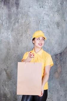 Kobieta kurier nosi żółty mundur dostarczając kartonową torbę na zakupy.