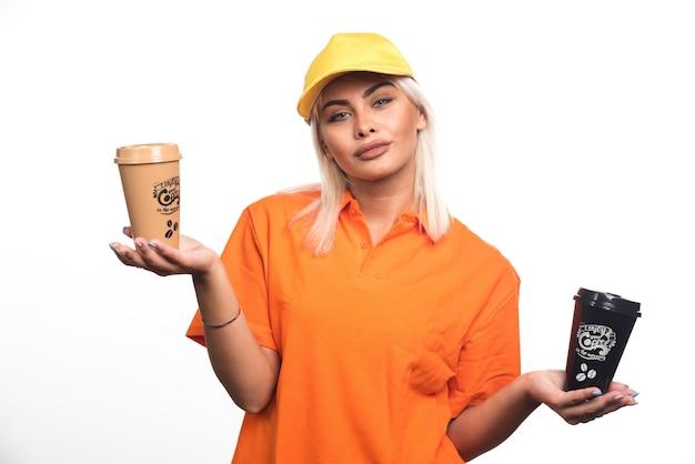 Kobieta kurier posiadający dwie filiżanki kawy na białym tle. wysokiej jakości zdjęcie