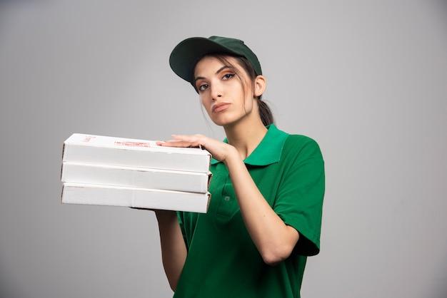 Kobieta kurier pozuje z pudełkami po pizzy